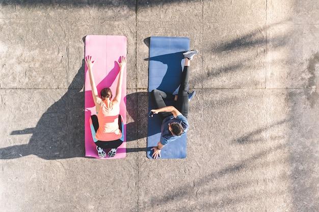 Hispanische paare, die draußen yoga tun.