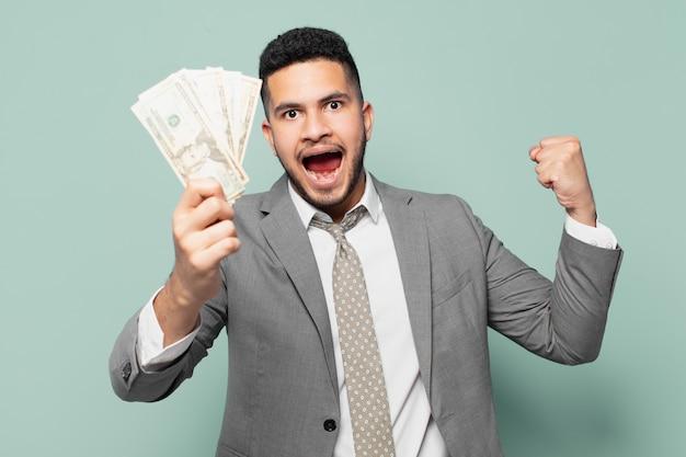 Hispanischer geschäftsmann, der erfolgreich einen sieg feiert und dollar-banknoten hält