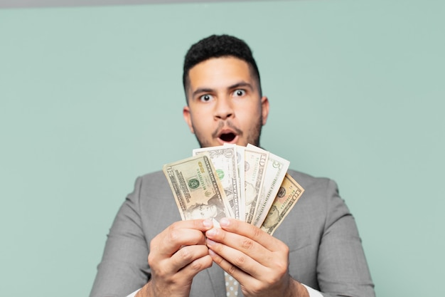 Hispanischer geschäftsmann erschrickt ausdruck und hält dollar-banknoten