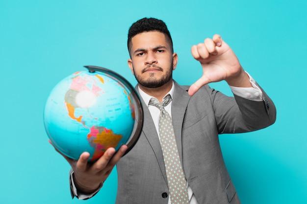Hispanischer geschäftsmann wütender ausdruck und hält ein weltplanetenmodell