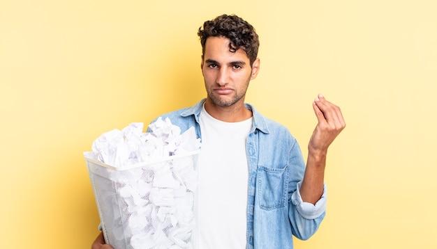 Hispanischer gutaussehender mann, der capice oder geldgeste macht und ihnen sagt, dass sie bezahlen sollen. papierkugeln müllkonzept