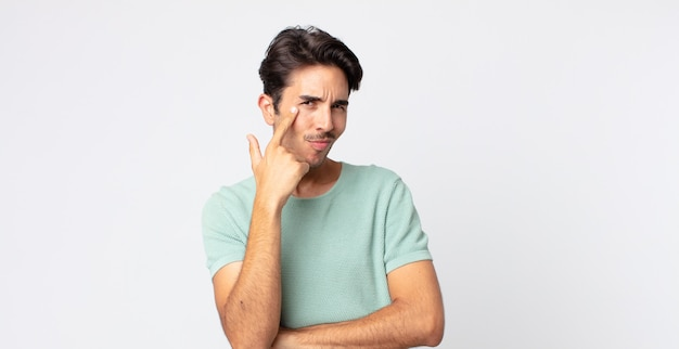 Hispanischer gutaussehender mann, der dich im auge behält, nicht vertraut, beobachtet und wachsam und wachsam bleibt