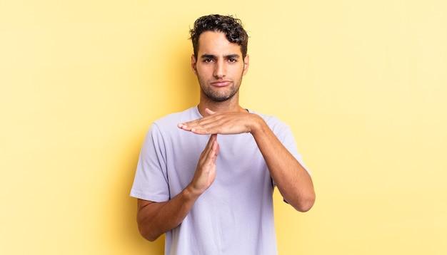 Hispanischer gutaussehender mann, der ernst aussieht und ein time-out-zeichen macht