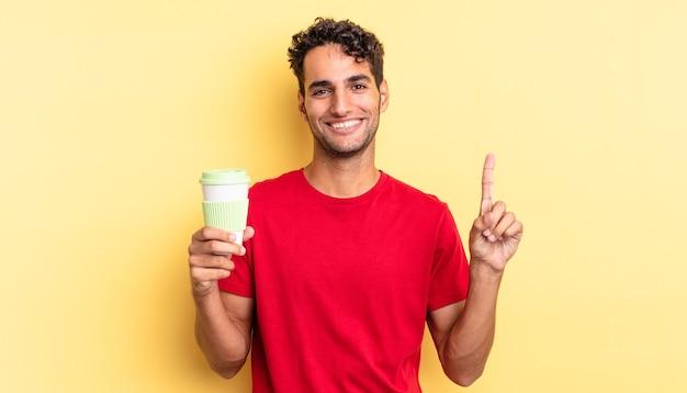 Hispanischer gutaussehender mann, der freundlich lächelt und aussieht und nummer eins zeigt. kaffee zum mitnehmen konzept