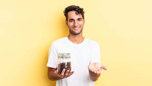 Hispanischer gutaussehender mann, der glücklich mit freundlichem lächeln lächelt und ein konzept anbietet und zeigt. kaffeebohnen flasche
