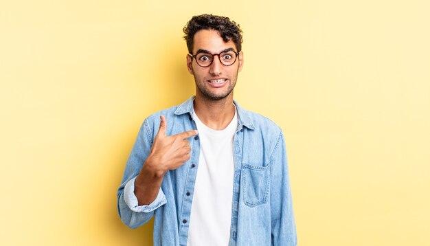 Hispanischer gutaussehender mann, der glücklich, stolz und überrascht aussieht und fröhlich auf sich selbst zeigt