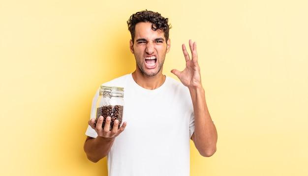 Hispanischer gutaussehender mann, der mit den händen in die luft schreit. kaffeebohnen flasche