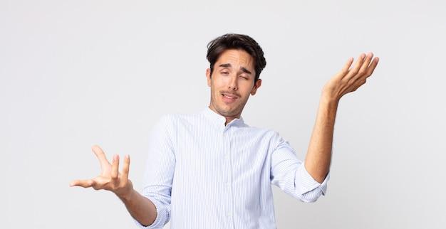 Hispanischer gutaussehender mann, der mit einem dummen, verrückten, verwirrten, verwirrten ausdruck die achseln zuckt und sich verärgert und ahnungslos fühlt