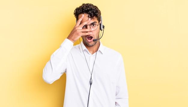 Hispanischer gutaussehender mann, der schockiert, verängstigt oder verängstigt aussieht und das gesicht mit der hand bedeckt. telemarketing-konzept