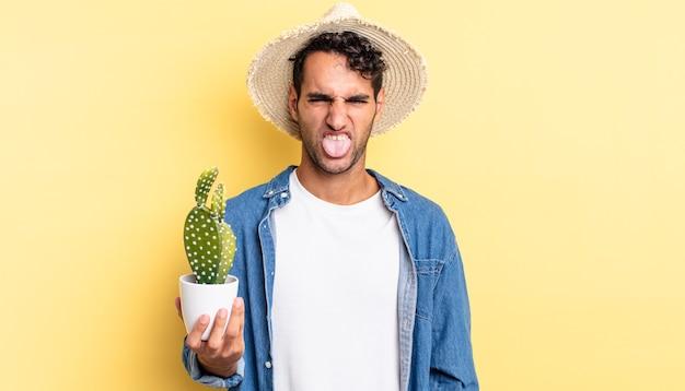 Hispanischer gutaussehender mann, der sich angewidert und irritiert fühlt und bauern- und kaktuskonzept mit der zunge herausstreckt