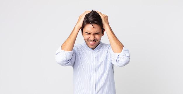 Hispanischer gutaussehender mann, der sich gestresst und frustriert fühlt, die hände zum kopf hebt, sich müde, unglücklich und mit migräne fühlt