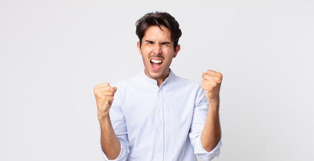 Hispanischer gutaussehender mann, der sich glücklich, positiv und erfolgreich fühlt und sieg, erfolge oder viel glück feiert