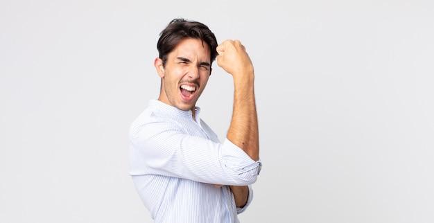 Hispanischer gutaussehender mann, der sich glücklich, zufrieden und kraftvoll fühlt, fit und muskulös ist und nach dem fitnessstudio stark aussieht