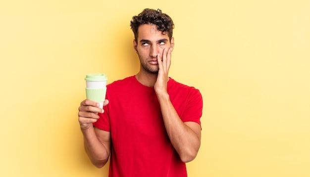 Hispanischer gutaussehender mann, der sich nach einem ermüdenden gefühl gelangweilt, frustriert und schläfrig fühlt. kaffee zum mitnehmen konzept