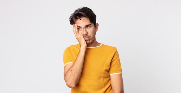 Hispanischer gutaussehender mann, der sich nach einer ermüdenden, langweiligen und langweiligen aufgabe gelangweilt, frustriert und schläfrig fühlt und das gesicht mit der hand hält