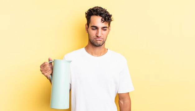 Hispanischer gutaussehender mann, der sich traurig, verärgert oder wütend fühlt und zur seite schaut. kaffee-thermos-konzept