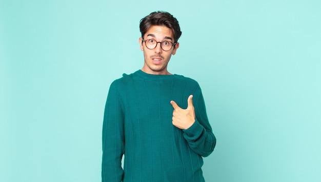 Hispanischer gutaussehender mann, der sich verwirrt, verwirrt und unsicher fühlt, auf selbstverwunderung deutet und fragt, wer, ich?