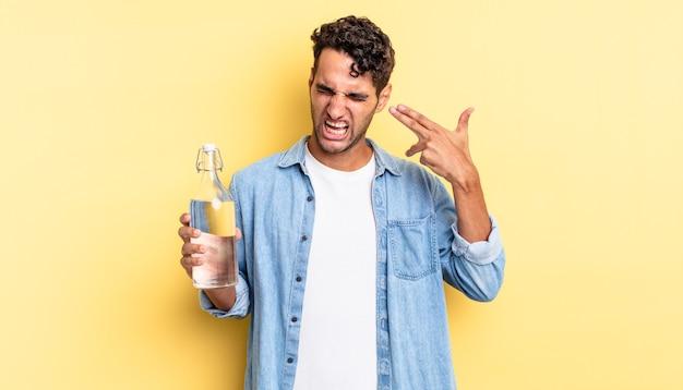 Hispanischer gutaussehender mann, der unglücklich und gestresst aussieht, selbstmordgeste, die waffenzeichen macht. wasserflaschenkonzept