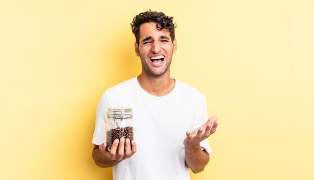 Hispanischer gutaussehender mann, der verzweifelt, frustriert und gestresst aussieht. kaffeebohnen flasche