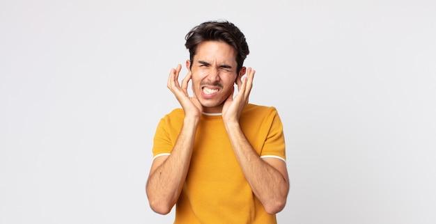 Hispanischer gutaussehender mann, der wütend, gestresst und verärgert aussieht und beide ohren vor einem ohrenbetäubenden geräusch, ton oder lauter musik bedeckt