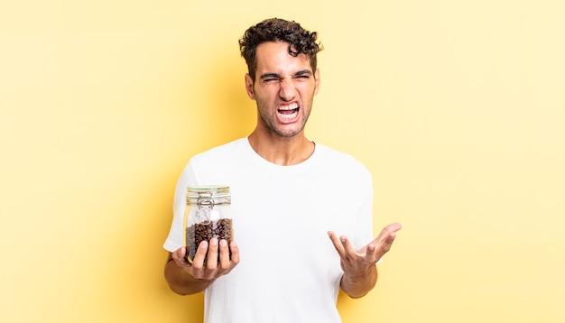Hispanischer gutaussehender mann, der wütend, verärgert und frustriert aussieht. kaffeebohnen flasche