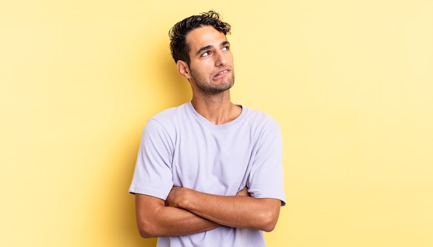 Hispanischer gutaussehender mann, der zweifelt oder denkt, auf die lippe beißt und sich unsicher fühlt