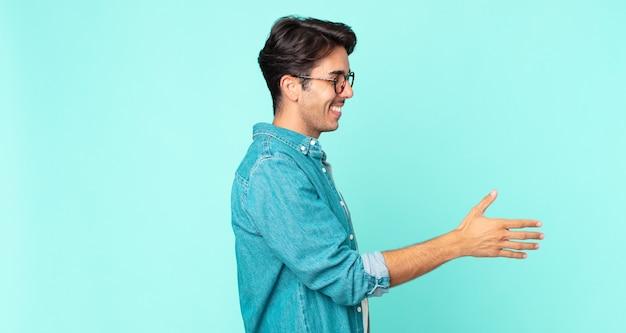 Hispanischer gutaussehender mann lächelt, begrüßt sie und bietet einen handschlag an, um ein erfolgreiches geschäft abzuschließen, kooperationskonzept