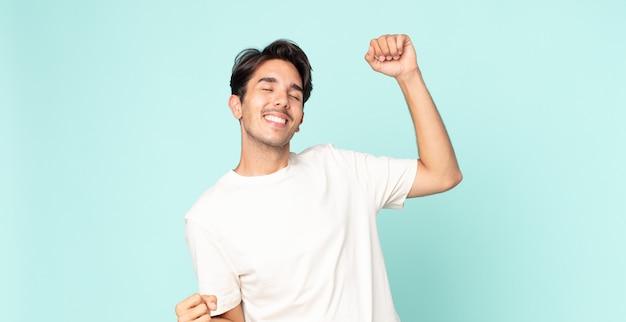 Hispanischer gutaussehender mann lächelt, fühlt sich sorglos, entspannt und glücklich, tanzt und hört musik, hat spaß auf einer party