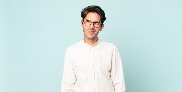 Hispanischer gutaussehender mann sieht glücklich und freundlich aus, lächelt und zwinkert ihnen mit einer positiven einstellung zu