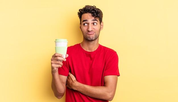 Hispanischer gutaussehender mann zuckt mit den schultern, fühlt sich verwirrt und unsicher. kaffee zum mitnehmen konzept