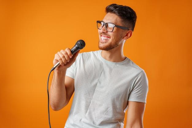Hispanischer junger hübscher mann, der mit freude im mikrofon clsoe oben singt