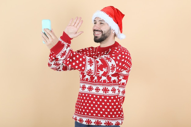 Hispanischer latino-mann mit weihnachtsmütze videoanruf per handy