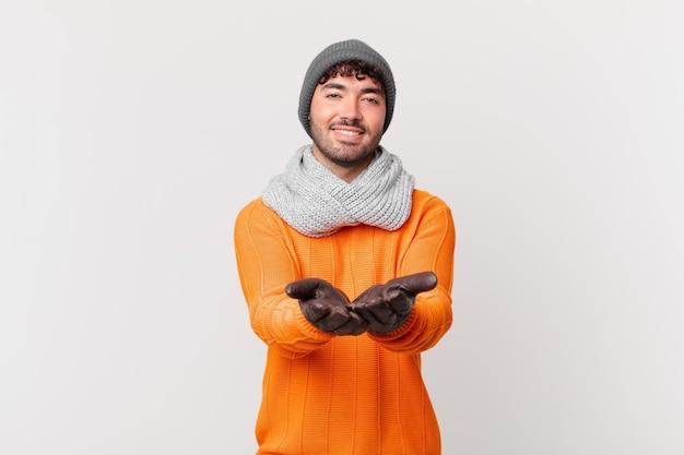 Hispanischer mann, der glücklich mit freundlichem, selbstbewusstem, positivem blick lächelt und ein objekt oder konzept anbietet und zeigt