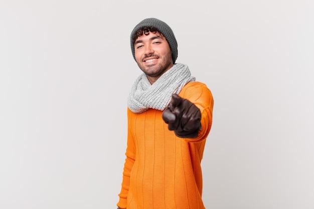 Hispanischer mann, der mit einem zufriedenen, selbstbewussten, freundlichen lächeln auf die kamera zeigt und sie wählt