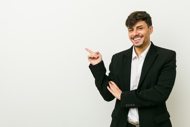 Hispanischer mann des jungen geschäfts, der mit dem zeigefinger weg freundlich zeigt lächelt