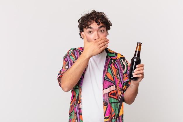 Hispanischer mann mit bier bedeckt den mund mit den händen mit einem schockierten, überraschten ausdruck, hält ein geheimnis oder sagt oops