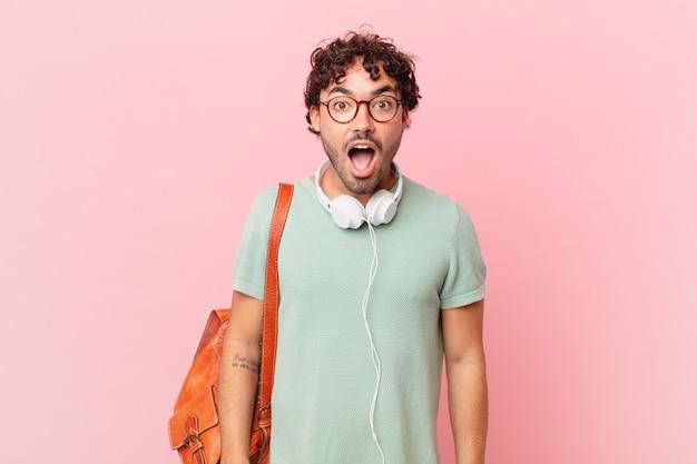 Hispanischer student, der sehr schockiert oder überrascht aussieht und mit offenem mund starrt und wow sagt