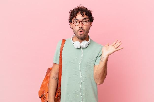 Hispanischer student, der überrascht und geschockt aussieht, mit gesenktem kiefer, der einen gegenstand mit einer offenen hand an der seite hält