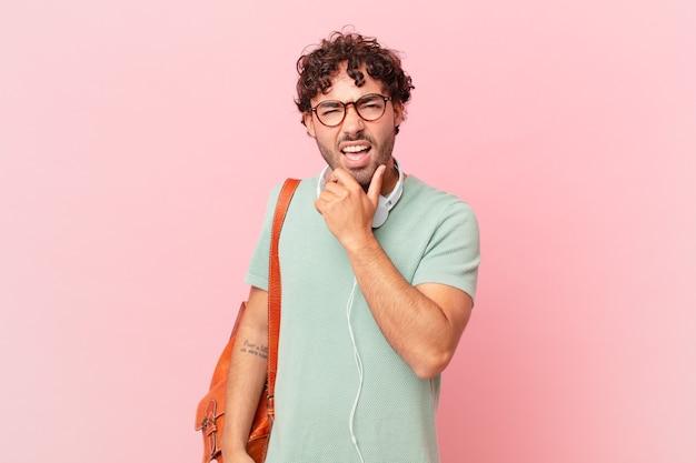 Hispanischer student mit offenem mund und weit geöffneten augen und hand am kinn, der sich unangenehm geschockt fühlt und sagt, was oder wow