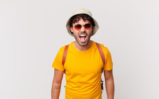 Hispanischer touristenmann, der aggressiv schreit, sehr wütend, frustriert, empört oder genervt aussieht und nein schreit