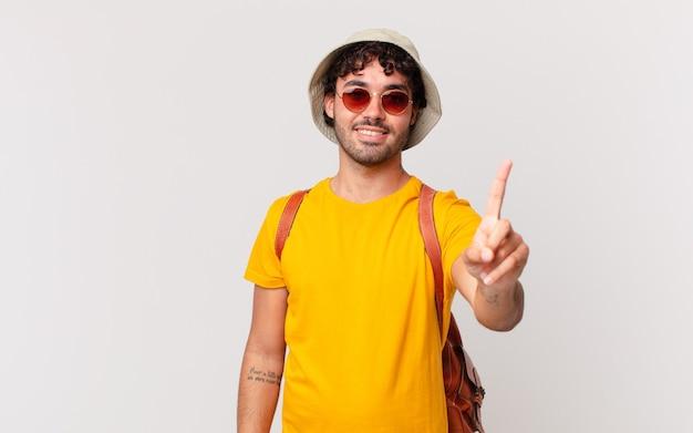 Hispanischer touristenmann, der lächelt und freundlich schaut, nummer eins oder zuerst mit der hand nach vorne zeigend, countdown