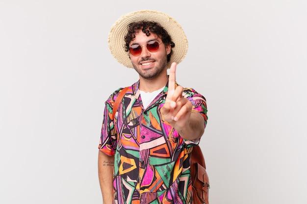 Hispanischer touristenmann, der stolz und zuversichtlich lächelt und nummer eins triumphierend posiert und sich wie ein führer fühlt