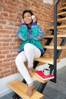 Hispanisches mädchen, das musik durch kopfhörer hört. sie sitzt auf der treppe ihres hauses neben einem buch und einer tasse kaffee.