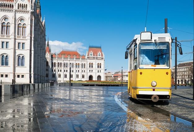 Historische tram, die durch parlament in budapest, ungarn überschreitet