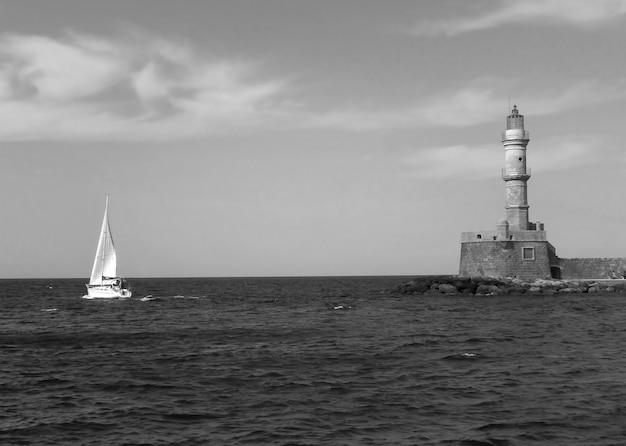Historischer leuchtturm des alten hafens von chania mit einem segelboot kreta griechenland in monochrom