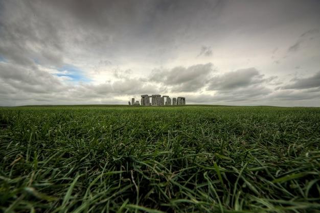 Historisches altes gebäude inmitten eines schönen grünen feldes unter dem düsteren himmel