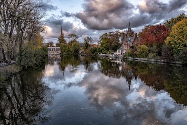 Historisches schloss, umgeben von bunten bäumen, die sich im see unter den gewitterwolken spiegeln