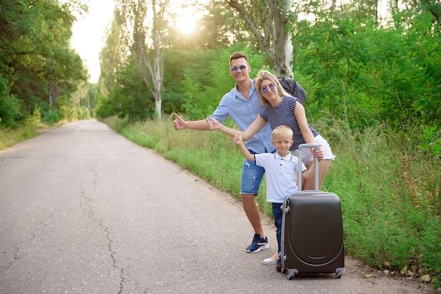 Hitch wandering des jungen familienreisenden auf leerer straße.