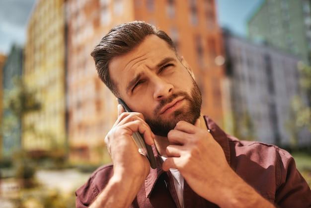 Hm... portrait eines nachdenklichen bärtigen mannes, der am telefon spricht und seine stoppeln berührt, während er auf der straße steht. schlechte nachrichten. digital. kommunikation