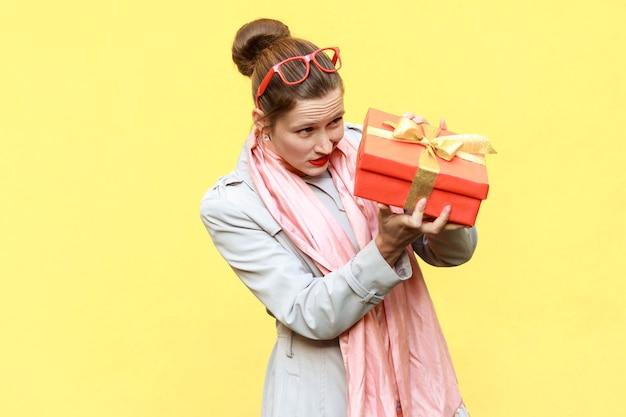 Hm, was ist das! schlaue frau, die geschenkbox betrachtet und zu offen möchte. gelber hintergrund. studioaufnahme